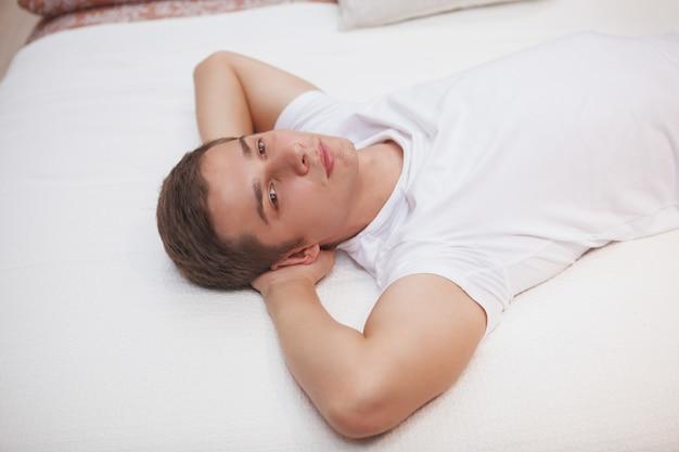 Jonge man ontspannen thuis, liggend in een bed