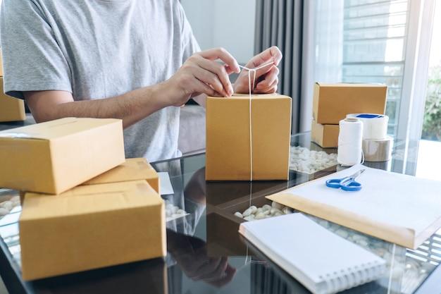 Jonge man ontvangt ordercliënt en werkt met verpakkingen