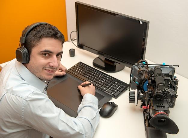 Jonge man ontwerper grafisch tablet gebruiken voor videobewerking