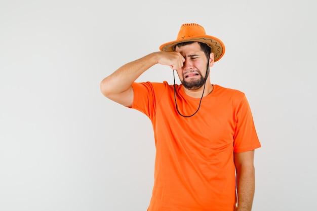 Jonge man oog wrijven terwijl huilen als een kind in oranje t-shirt, hoed en beledigd, vooraanzicht kijken.