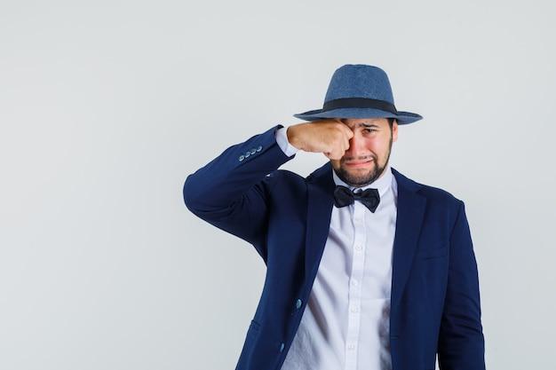 Jonge man oog wrijven terwijl huilen in pak, hoed vooraanzicht.