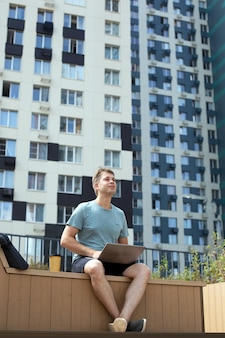 Jonge man op afstand buitenshuis werken. man zit met laptop en koffie in de moderne wijk. verticaal formaat