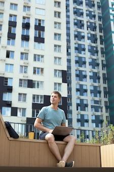 Jonge man op afstand buitenshuis werken. man zit met laptop en koffie in de moderne wijk