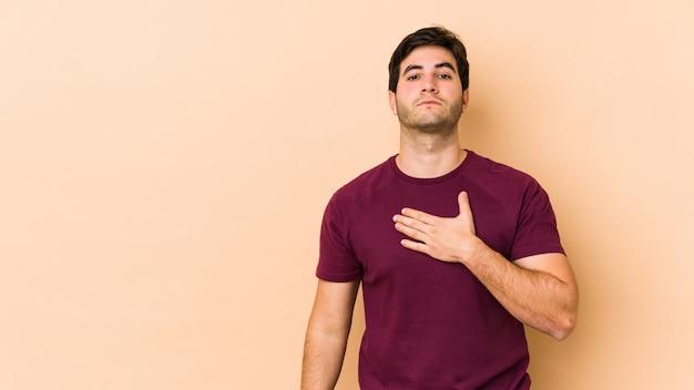 Jonge man op beige muur een eed afleggen, hand zetten op de borst.