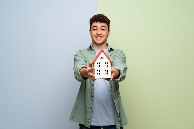 Jonge man op blauw en op groen met een klein huis