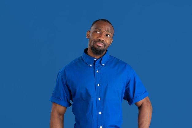 Jonge man op blauwe studiomuur