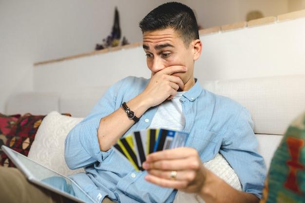 Jonge man op de bank thuis met tablet online winkelen.