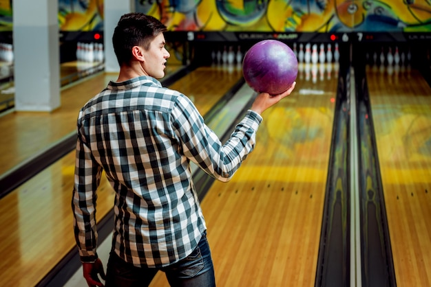 Jonge man op de bowlingbaan met de bal.