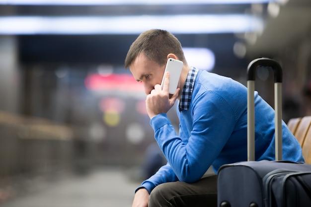 Jonge man op de telefoon op de luchthaven