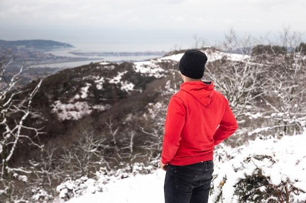 Jonge man op de top van een besneeuwde berg met een rode trui en zwarte spijkerbroek.