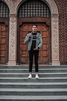 Jonge man op de trappen van een oud gebouw