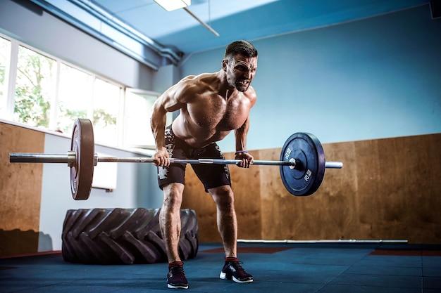 Jonge man op een crossfit gym een barbell opheffen.