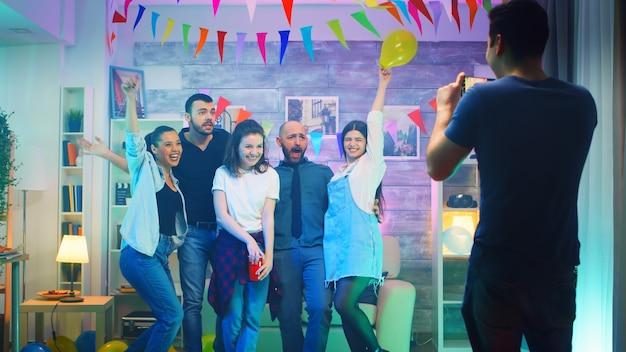 Jonge man op een feestje die foto's maakt van zijn vrienden met een smartphone. vrolijke groep mensen.