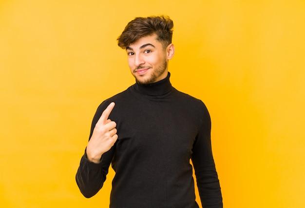 Jonge man op een gele muur wijzend met vinger naar je alsof uitnodigen dichterbij komen.
