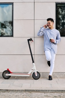 Jonge man op een scooter praten aan de telefoon