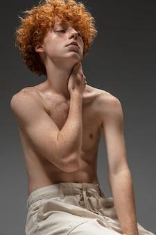 Jonge man op grijze muur, studio. mooie roodharige