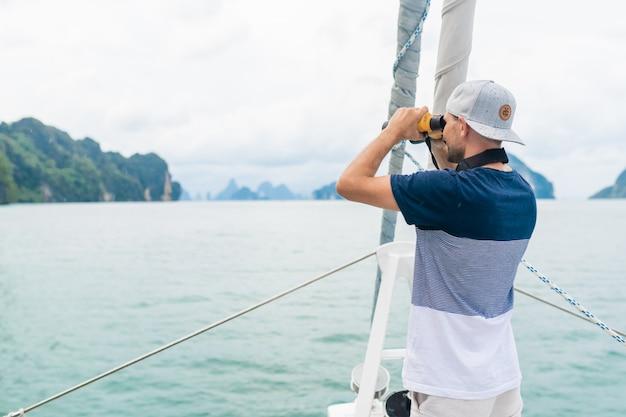 Jonge man op het jacht kijkt door een verrekijker. reizen en actief leven.