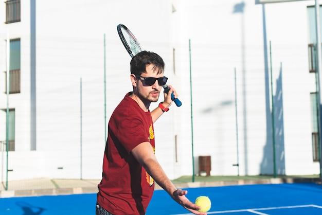 Jonge man op het punt om de tennisbal met het racket te raken.