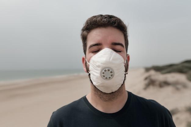 Jonge man op het strand draagt een medisch masker om ziekten en virussen te voorkomen