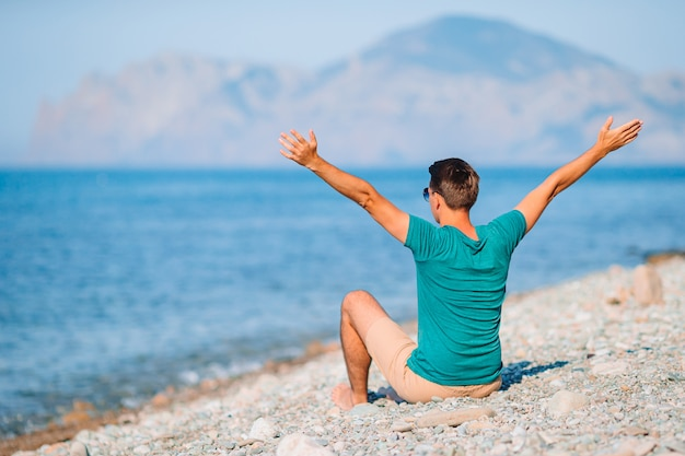 Jonge man op het strand ontspannen met uitzicht op de bergen