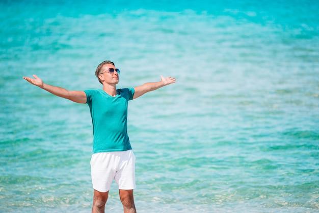 Jonge man op het witte strand op vakantie