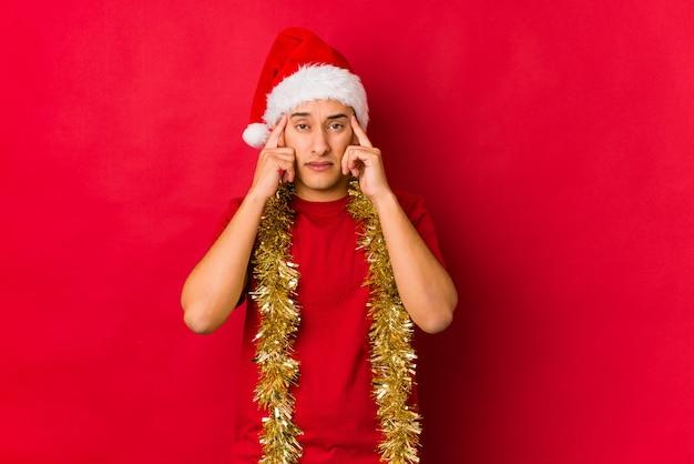 Jonge man op kerstdag gericht op een taak, wijsvingers hoofd houden.