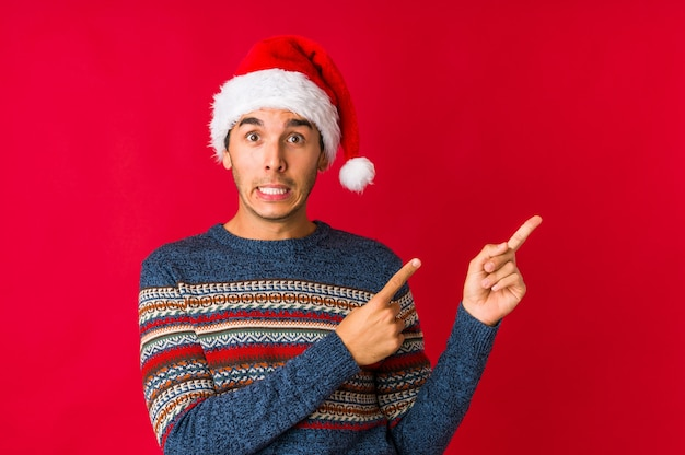 Jonge man op kerstdag glimlachend vrolijk wijzend met wijsvinger weg.