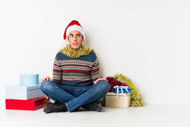 Jonge man op kerstdag glimlacht, vingers naar mond wijzend.