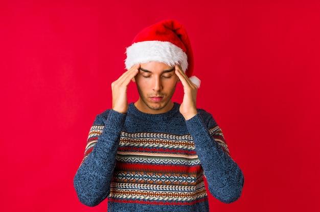 Jonge man op kerstdag viert een speciale dag, springt en hef wapens met energie.