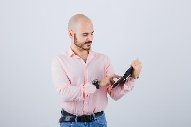 Jonge man op knoppen van rekenmachine in roze shirt, jeans vooraanzicht.