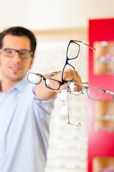 Jonge man op opticien met een bril