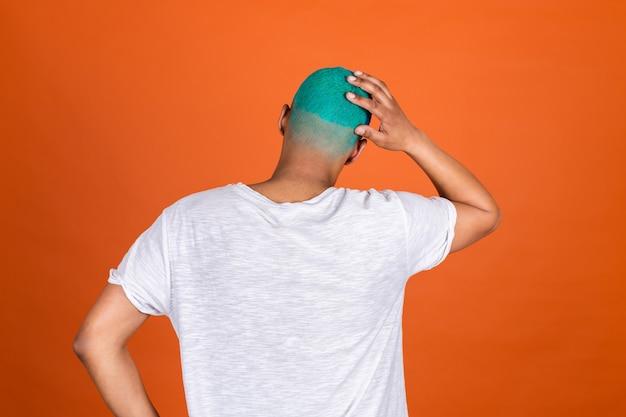 Jonge man op oranje muur terug naar camera houdt hoofd bedachtzaam