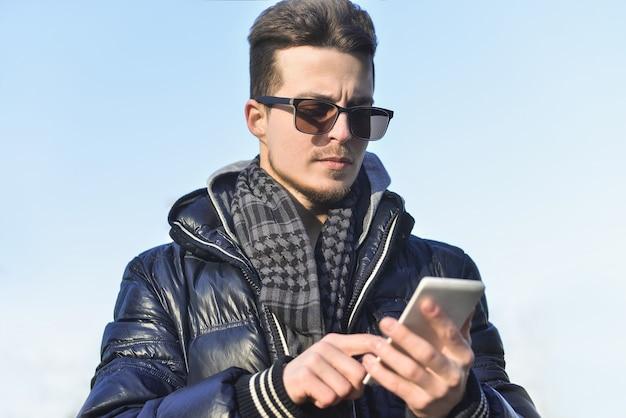 Jonge man op straat, chatten aan de telefoon