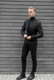 Jonge man op straat die zijn jas sluit