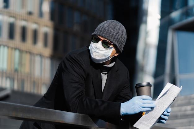 Jonge man op straat met afhaalmaaltijden koffie en krant, draagt beschermend medisch masker en handschoenen, voorkomt verspreiding van coronavirus, kijkt peinzend opzij, poseert buiten. covid-19 pandemie, quarantaine