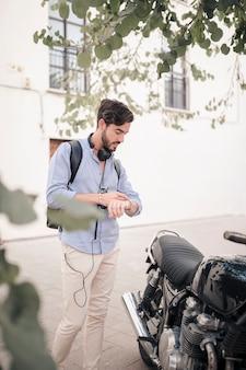 Jonge man op tijd op horloge in de buurt van zijn motor kijken