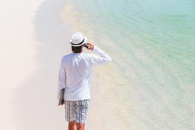 Jonge man op tropisch strand in de buurt van watervilla