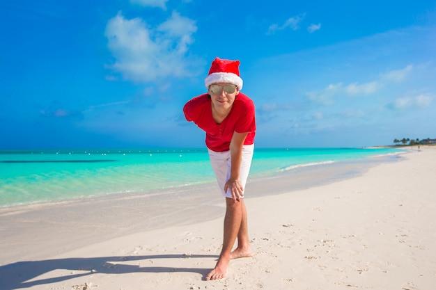Jonge man op tropisch strand in kerstmuts