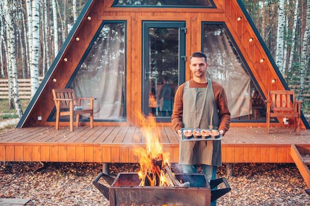 Jonge man op warme herfst dag grill buitenshuis