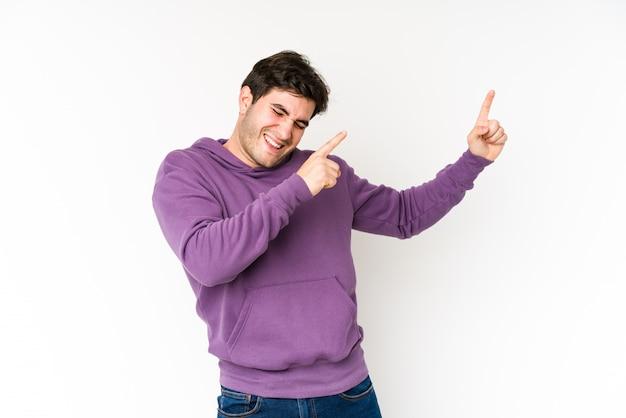 Jonge man op witte muur dansen en plezier maken.