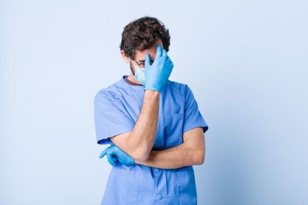 Jonge man op zoek beklemtoond, beschaamd of boos, met hoofdpijn, gezicht met de hand bedekkend. coronavirus concept