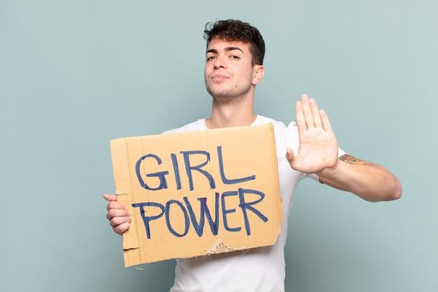 Jonge man op zoek ernstig, streng, ontevreden en boos met open palm stop gebaar maken