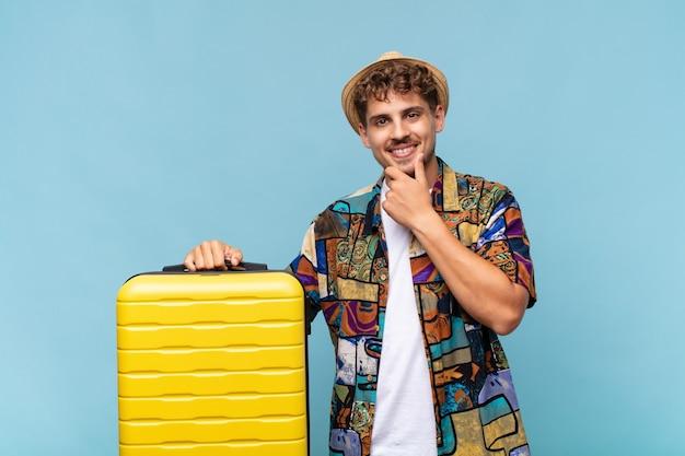 Jonge man op zoek gelukkig en lachend met de hand op de kin, zich afvragend of een vraag te stellen, opties te vergelijken