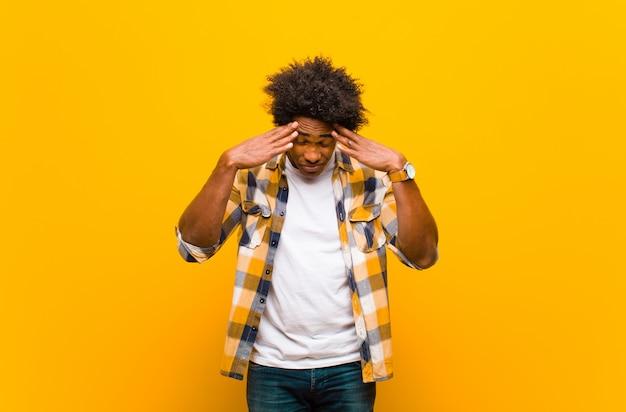 Jonge man op zoek gestrest en gefrustreerd, werkt onder druk met hoofdpijn en last van problemen over oranje muur