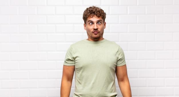 Jonge man op zoek goofy en grappig met een dwaze schele uitdrukking geïsoleerd