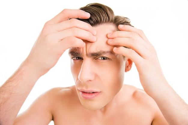 Jonge man op zoek naar acnes op zijn gezicht