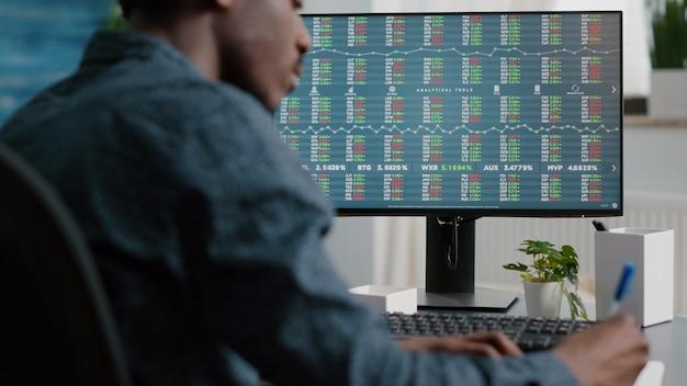 Jonge man op zoek naar crypto valuta aandelenmarkt stock