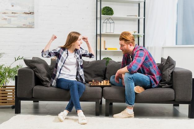 Jonge man op zoek naar haar vriendin juichen met succes tijdens het spelen van schaak