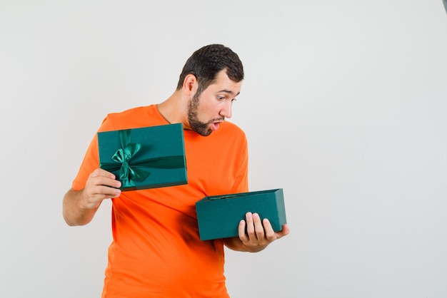 Jonge man op zoek naar huidige doos in oranje t-shirt en op zoek benieuwd, vooraanzicht.