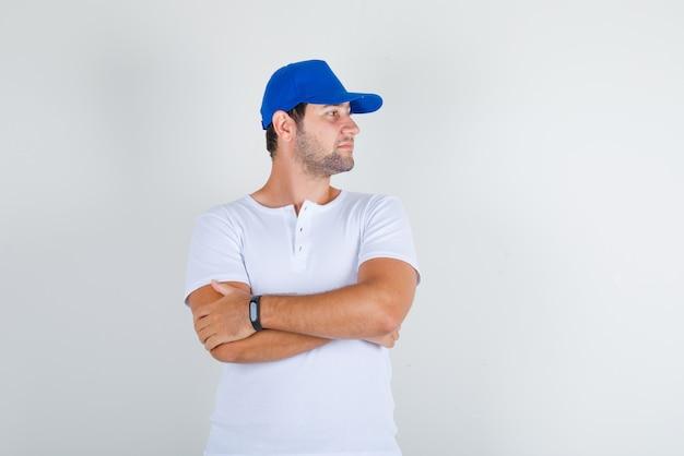 Jonge man op zoek naar kant met gekruiste armen in wit t-shirt met blauwe pet